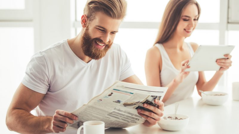 Beautiful young couple is having a breakfast together at home. Girl is using a digital tablet, guy is reading a newspaper